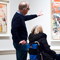 A person showing another visitor a painting